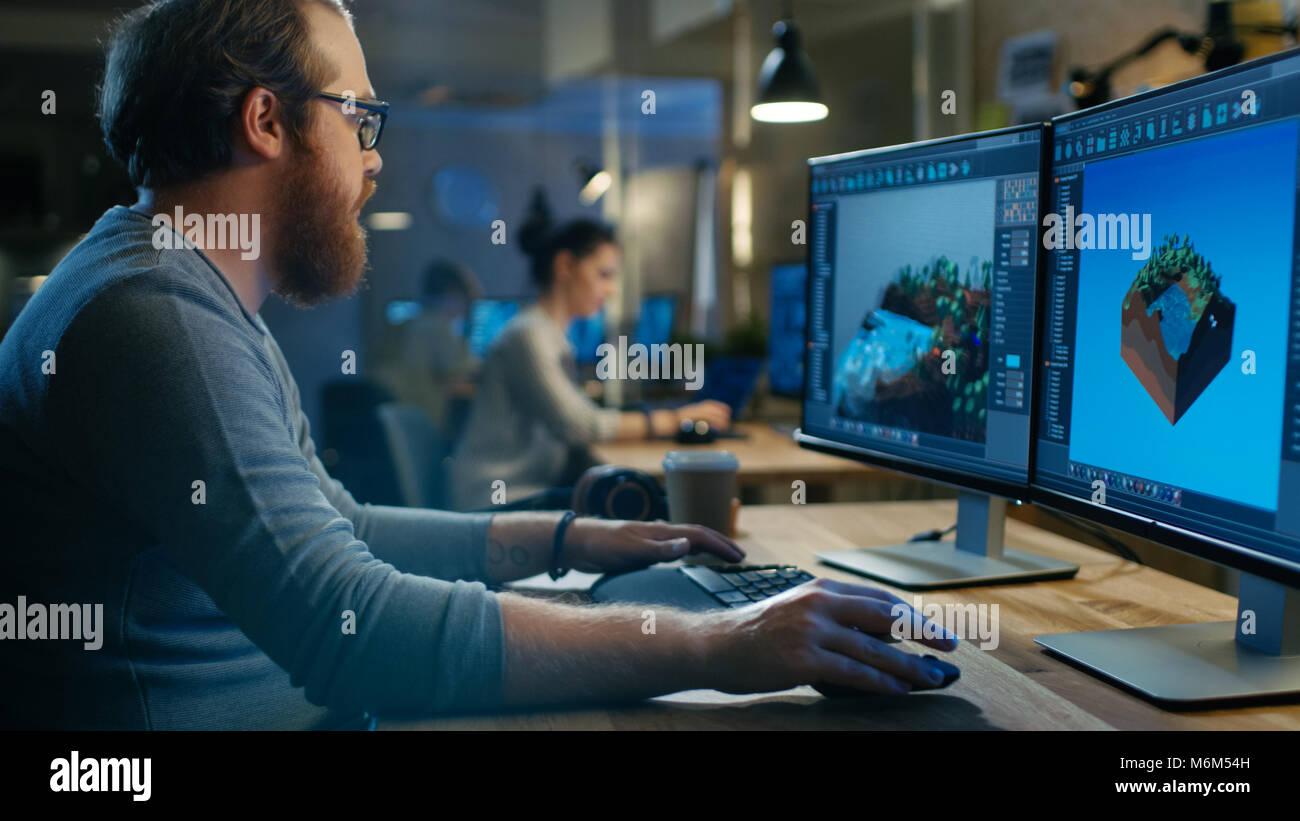 Maschio creativo sviluppatore del gioco funziona con la grafica per il nuovo livello di progettazione, si siede Immagini Stock