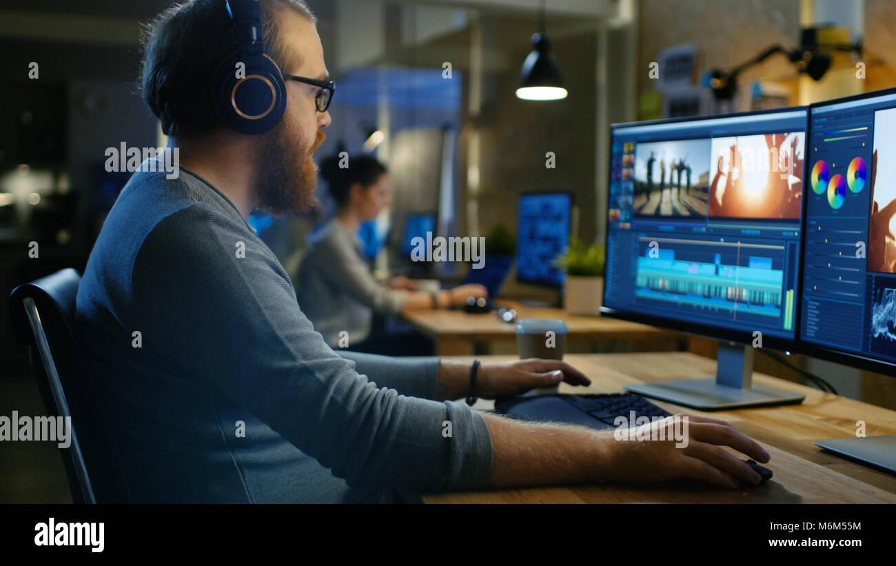 Videografo maschio modifiche e tagli di filmati e audio sul suo personal computer, mette sul suo monitor/ Cuffie. Immagini Stock