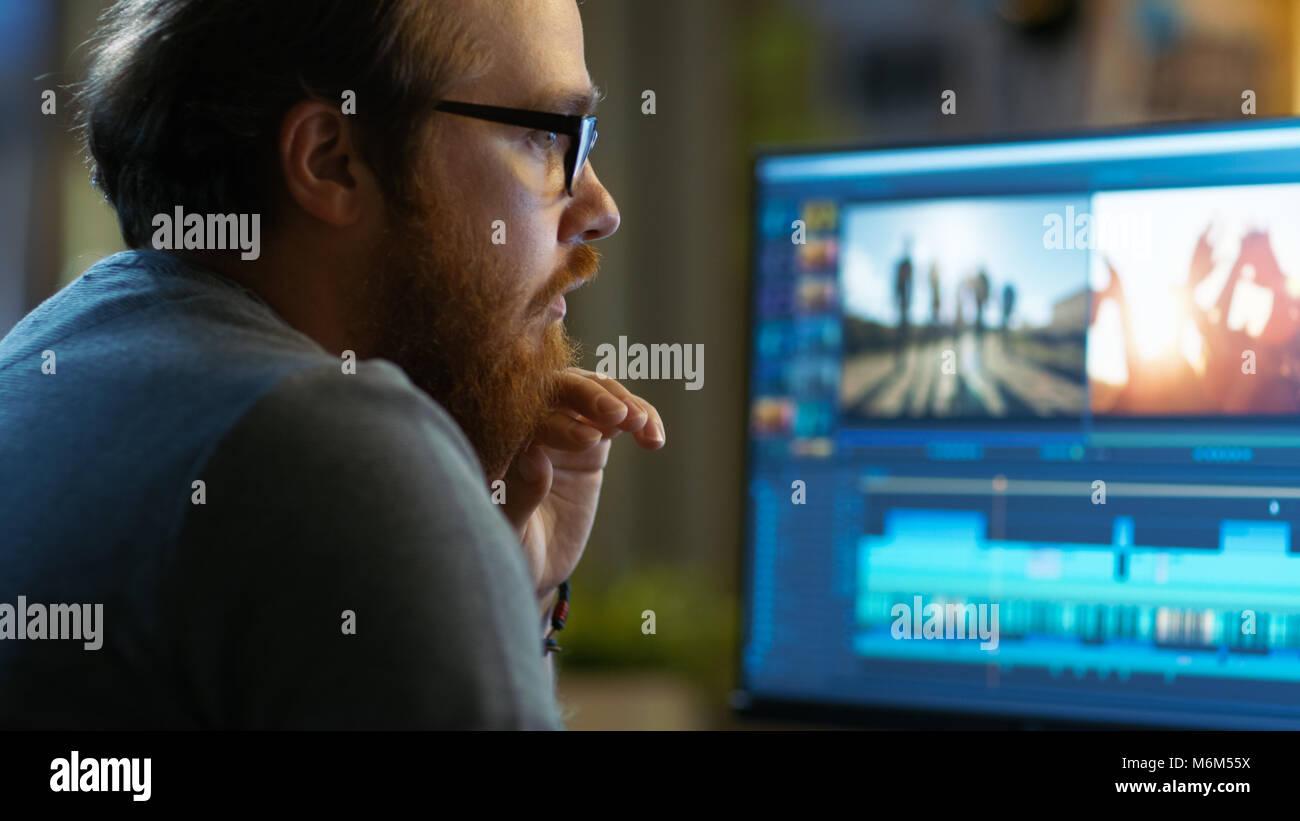 Maschio Editor video funziona con filmati e audio sul suo personal computer. Egli lavora in un ufficio fresco Loft. Immagini Stock