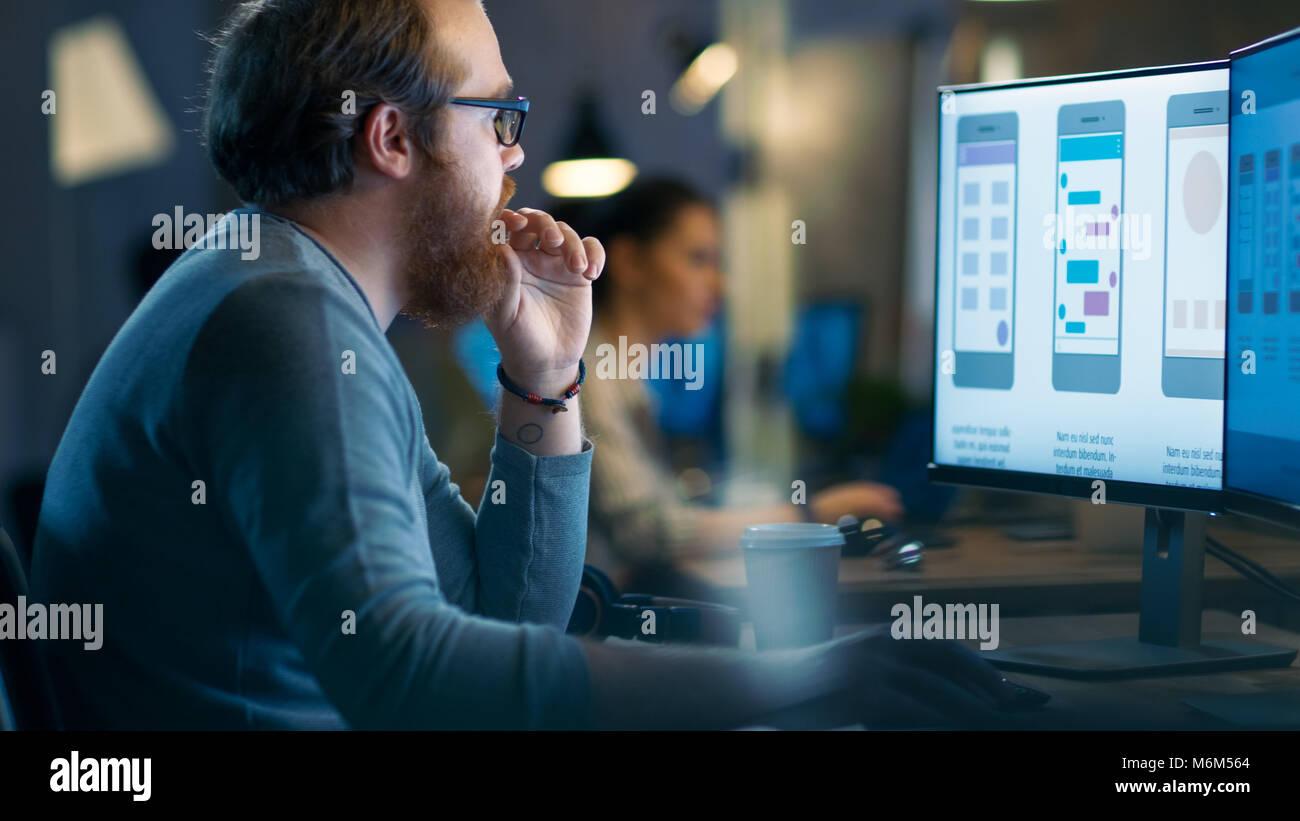 Maschio di Mobile Application Developer lavora con grafica sul Suo Personal Computer con due monitor. Egli condivide Immagini Stock