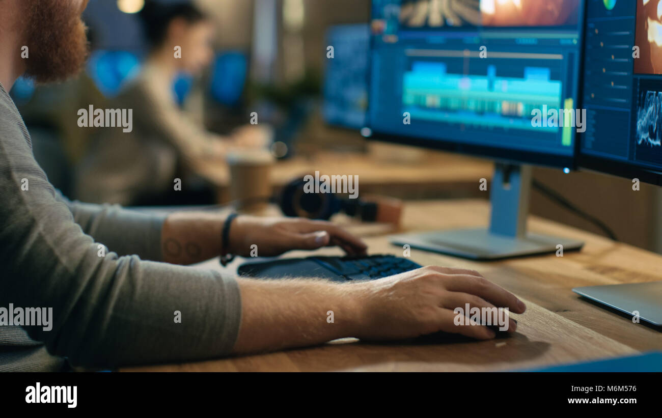 Videografo maschio modifiche e tagli di filmati e audio sul suo personal computer con due schermi. Il suo ufficio Immagini Stock