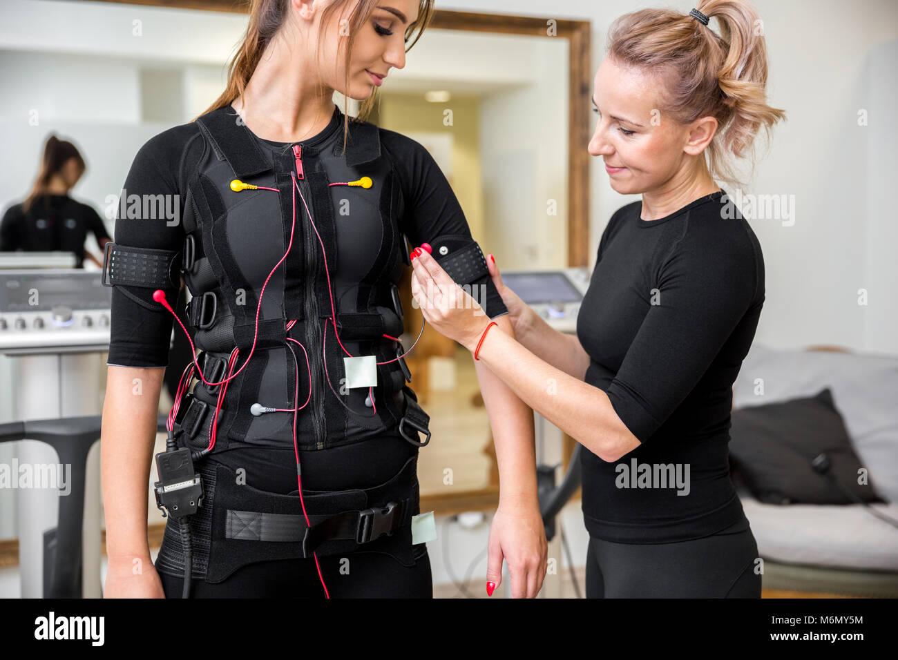 Ritratto di personal trainer immissione ems diodi sul giovane donna Immagini Stock