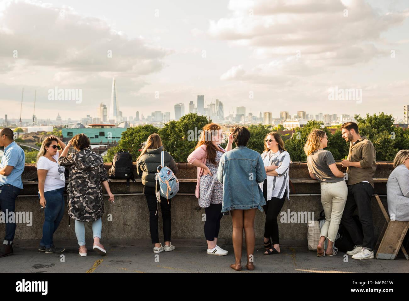 La gente di socializzare e gustare un drink insieme a Franchi outdoor cafe bar sul tetto con vista della città. Immagini Stock