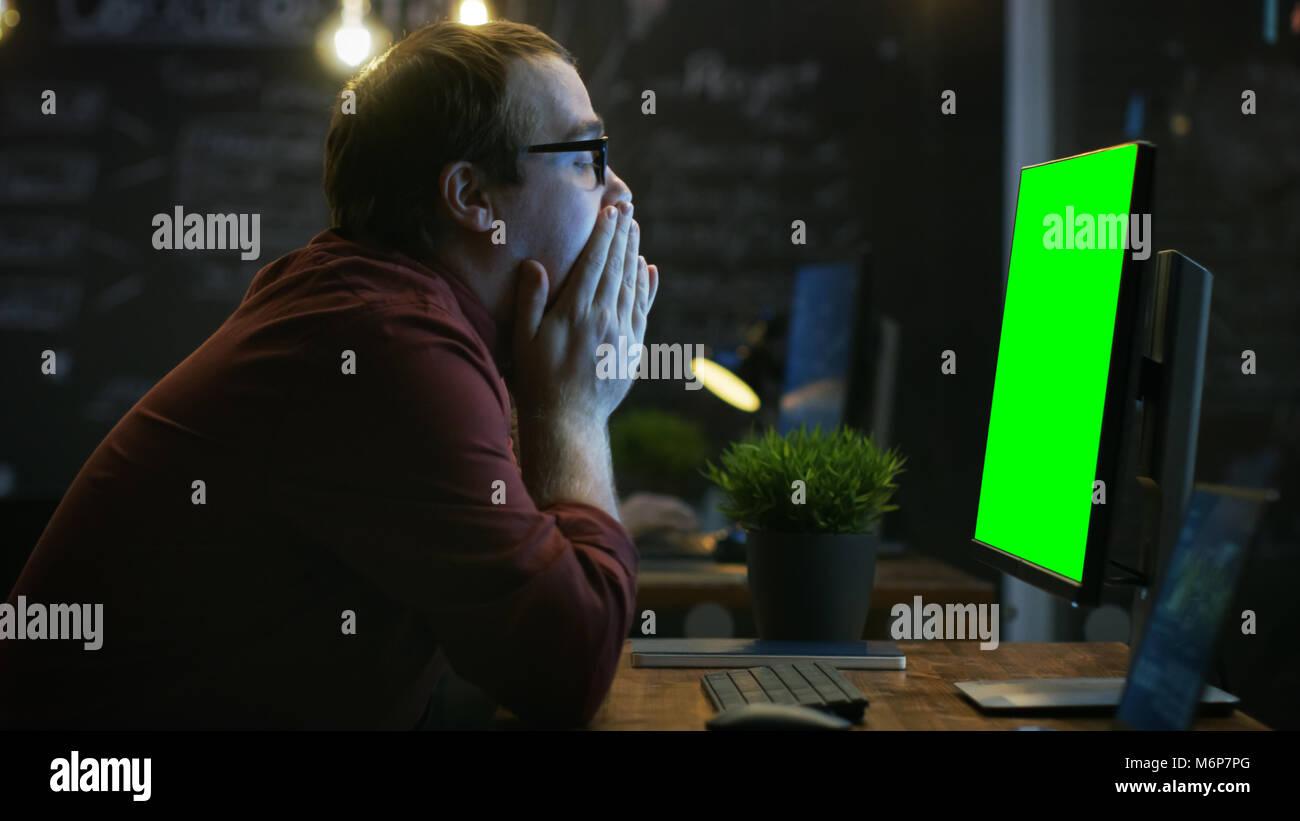 Sottolineato lavoratore di ufficio, esala e colpisce il tavolo con il pugno di frustrazione e copre il volto con Immagini Stock