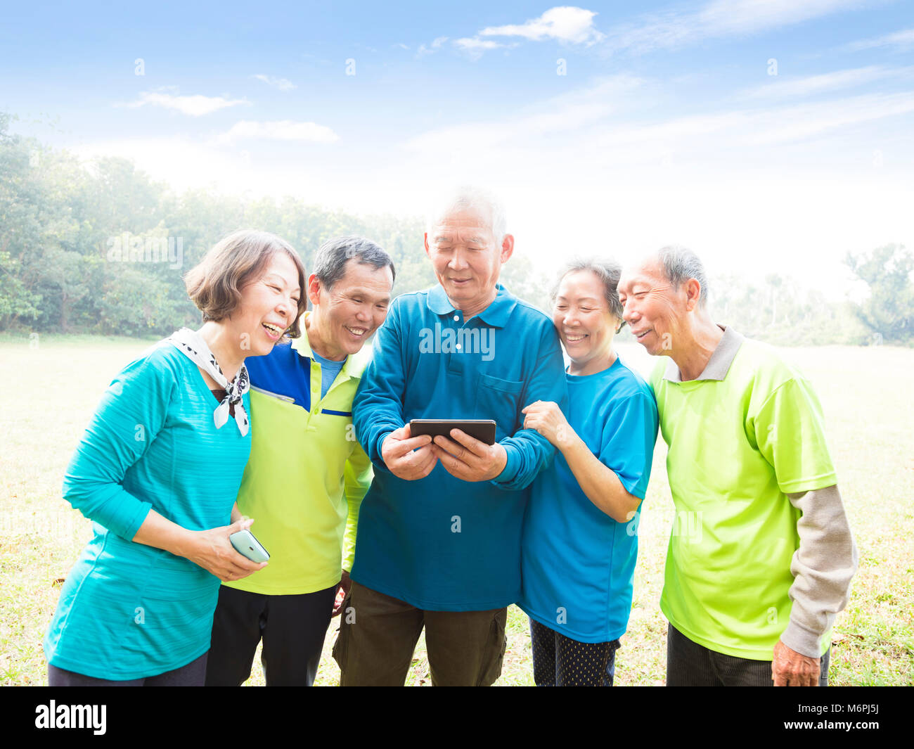 Gruppo di anziani a guardare la smart phone Foto Stock