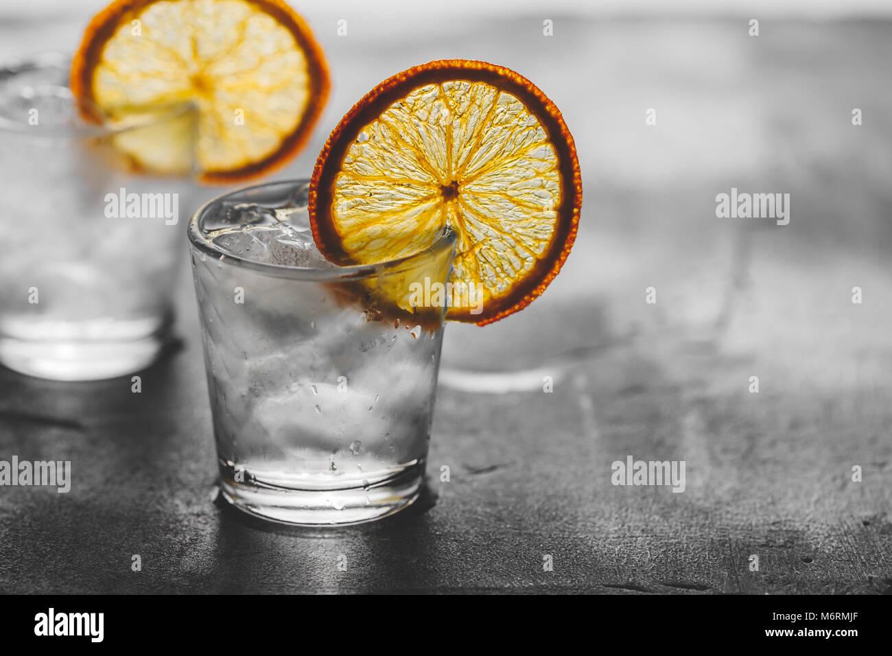 Due colpi di tequila con ghiaccio e una secca fetta di colore arancione su sfondo grigio. Immagini Stock