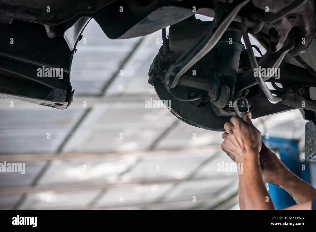 Auto meccanico controllo asiatico bush-bullone sotto doppio triangolo sospensione a mano con strumenti ascensore Immagini Stock