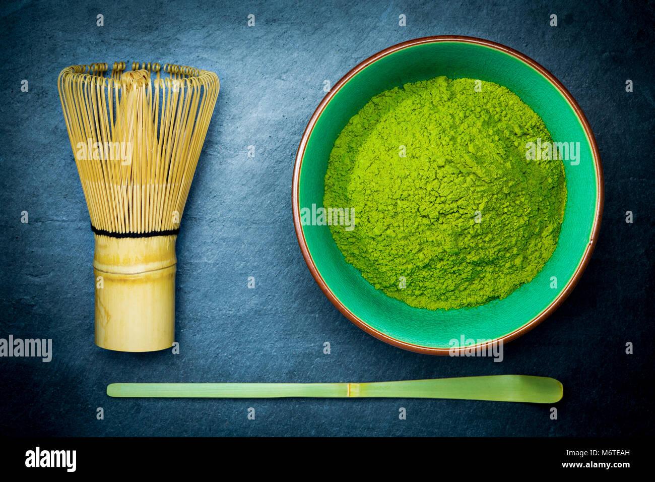 Tè verde Matcha in polvere in una ciotola con una frusta di bambù e cucchiaio su ardesia scuro dello sfondo. Immagini Stock