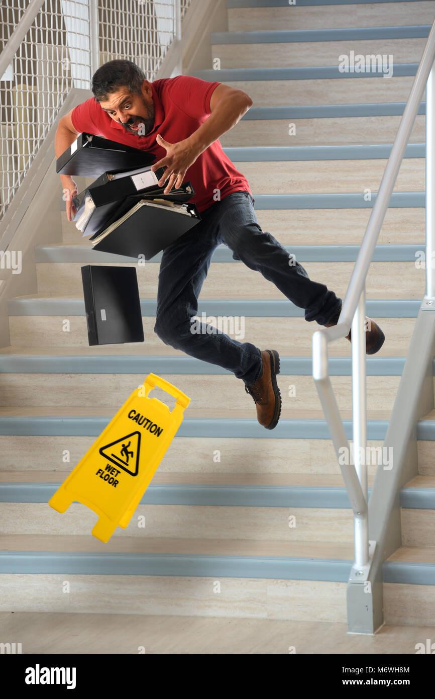 Lavoratore ispanica che trasportano i file cadendo sul bagnato scale ...