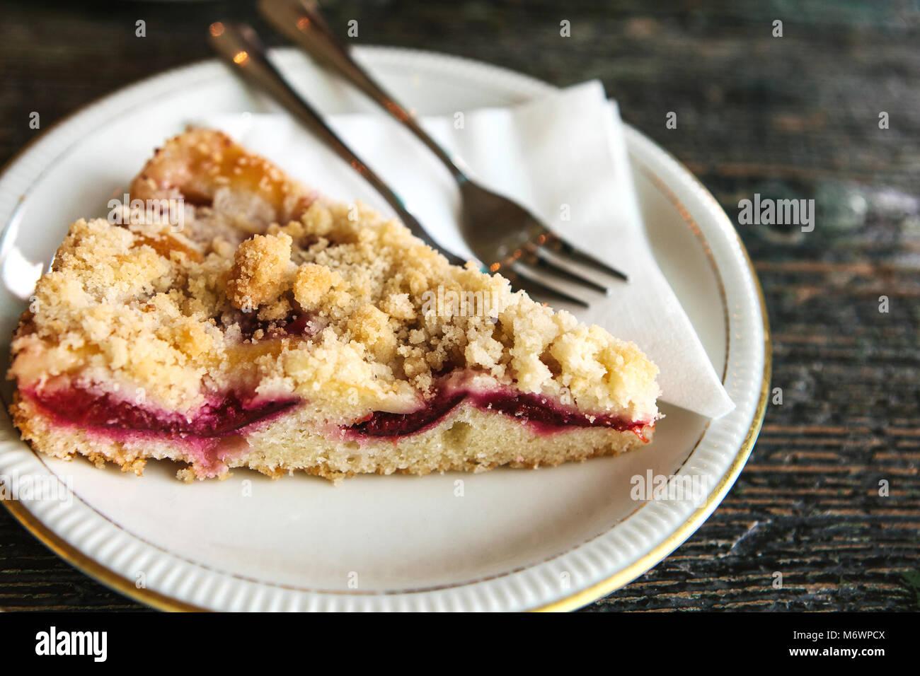 Pezzo di torta dolce con dessert forcella su una piastra su una superficie di legno in cafe Immagini Stock