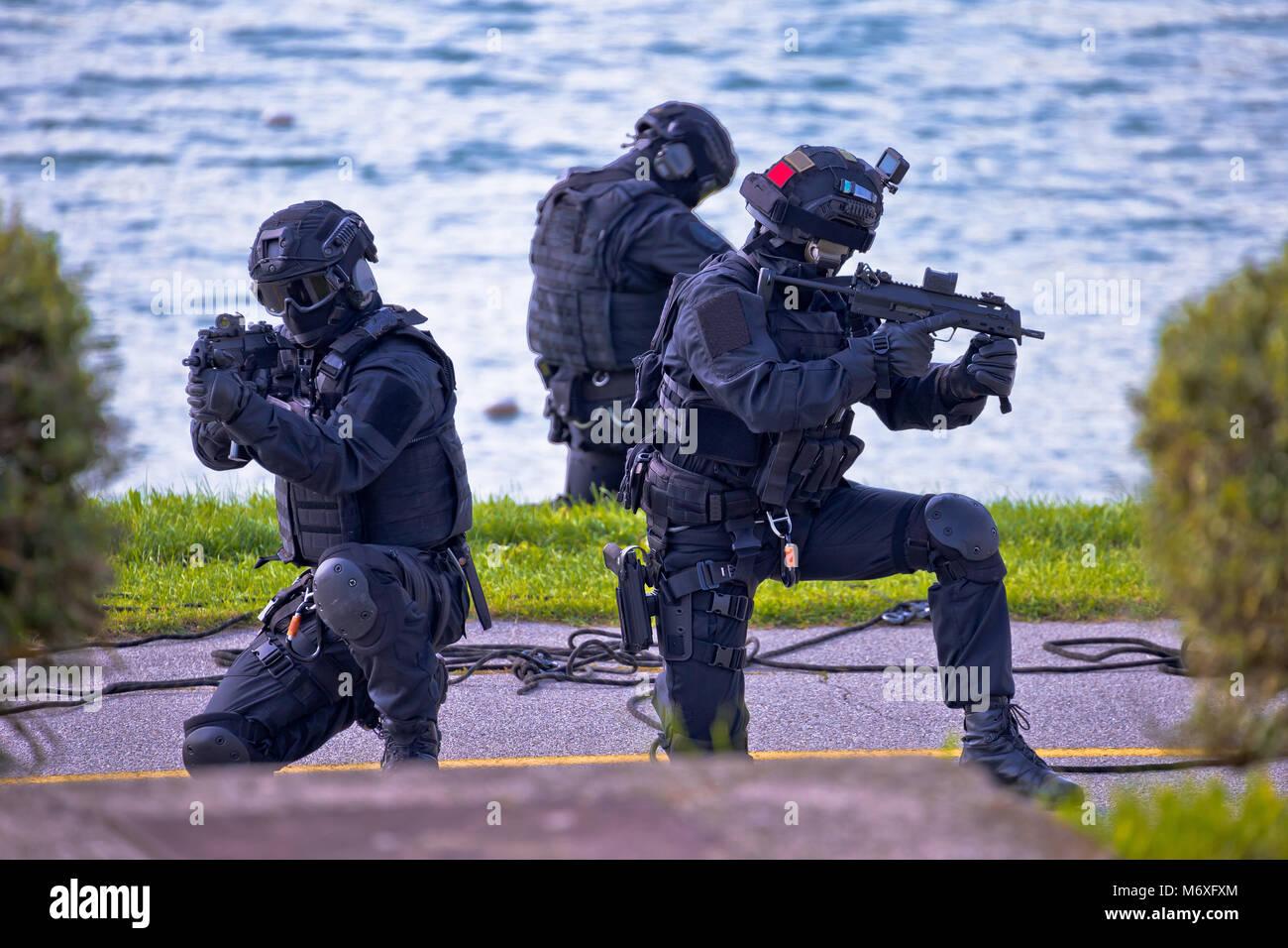 Le forze speciali tattiche di squadra di tre in azione, non marcati e irriconoscibile SWAT team Immagini Stock