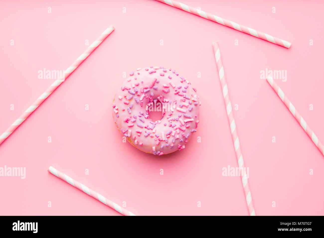 Ciambella rosa e paillette rosa su sfondo rosa. Immagini Stock