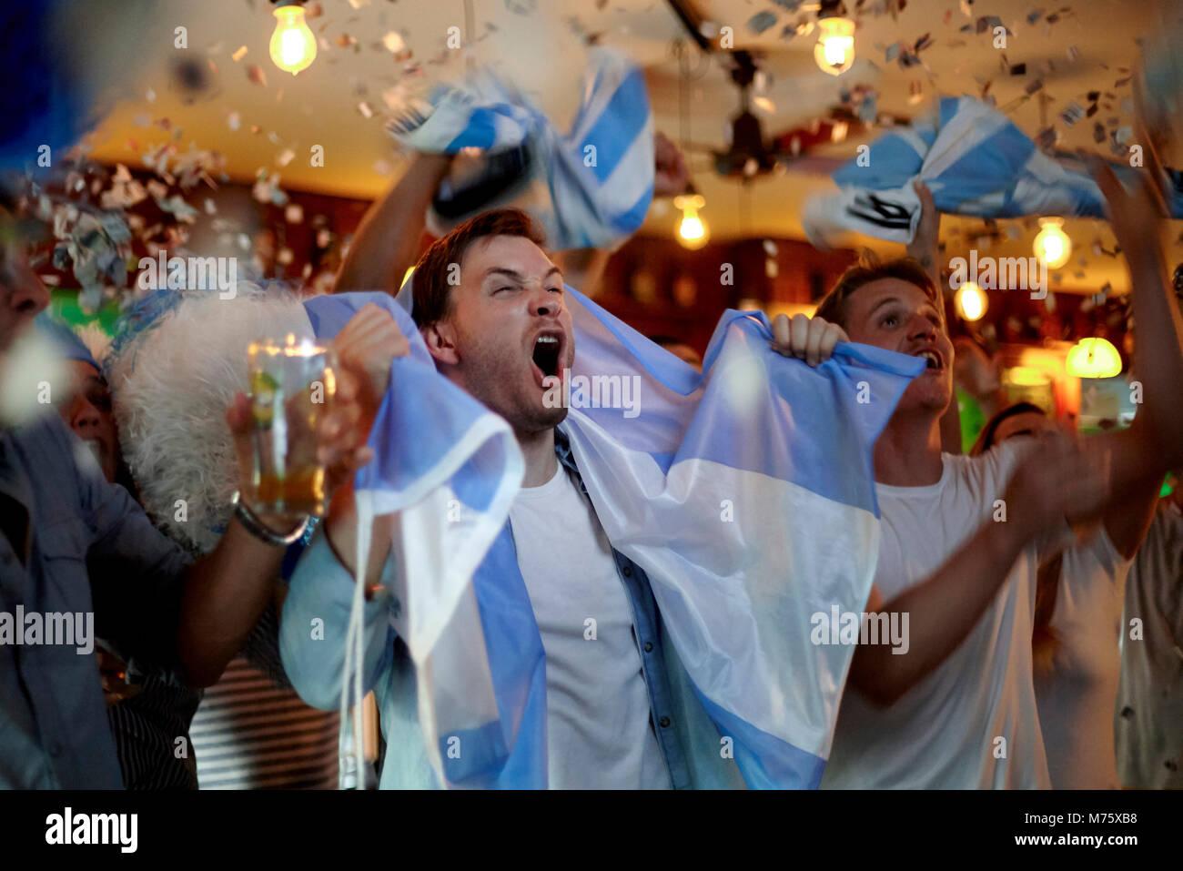 Il calcio argentino ventole celebrando la vittoria in bar Immagini Stock