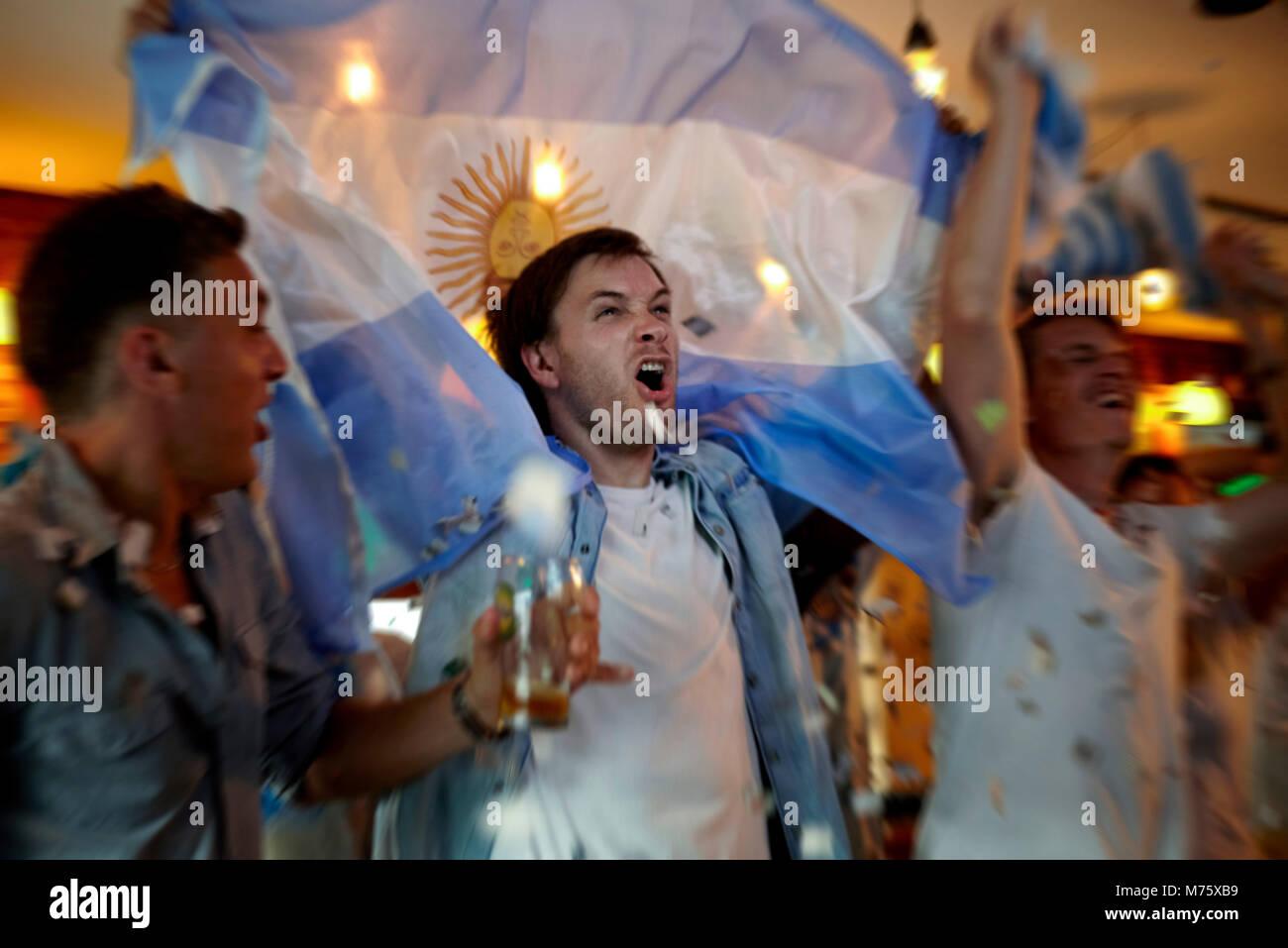 Il calcio argentino ventole celebrando in bar Immagini Stock