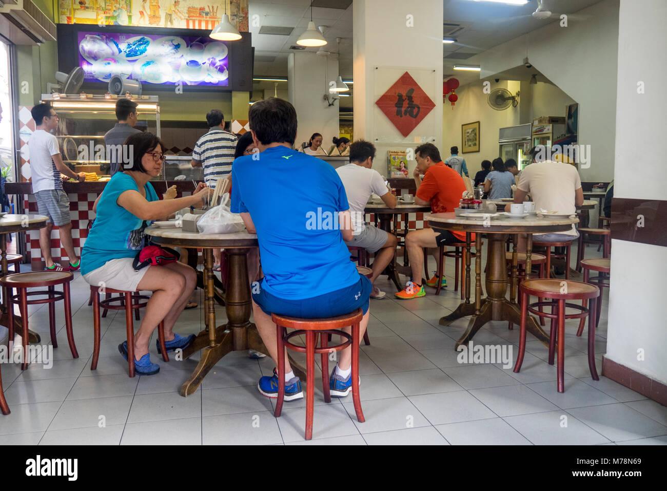 Abitanti di Singapore locali seduti in un tradizionale ristorante di Singapore, YY Kafei Dian per colazione. Immagini Stock