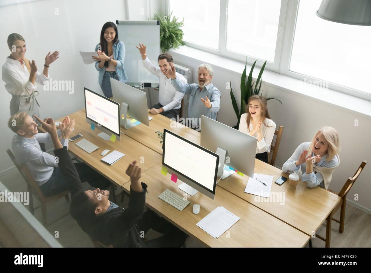 Entusiasta team diversificato congratulazioni collega nero con ottenere Immagini Stock