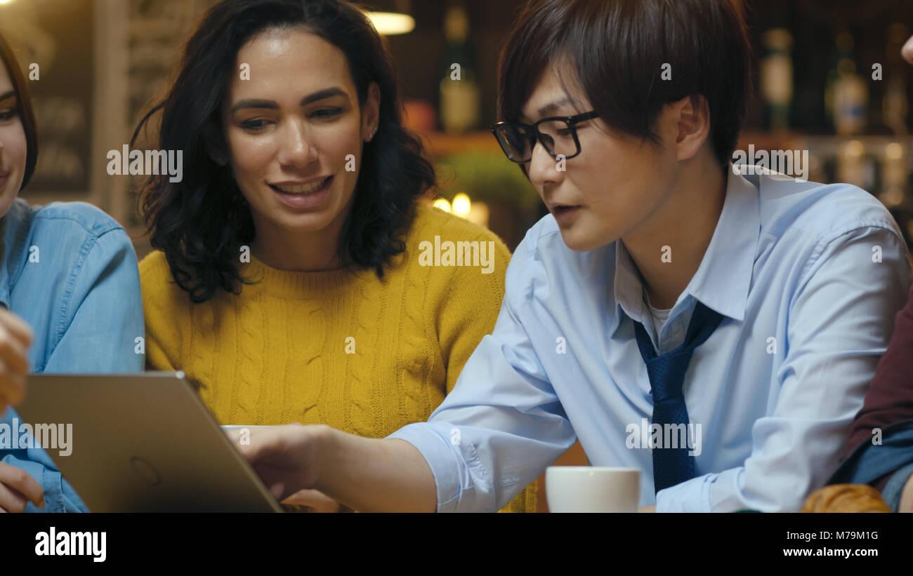 Diversi gruppi di colleghi ha business lunch presso il cafe/ristorante, pensano a risolvere i problemi e di utilizzare Foto Stock