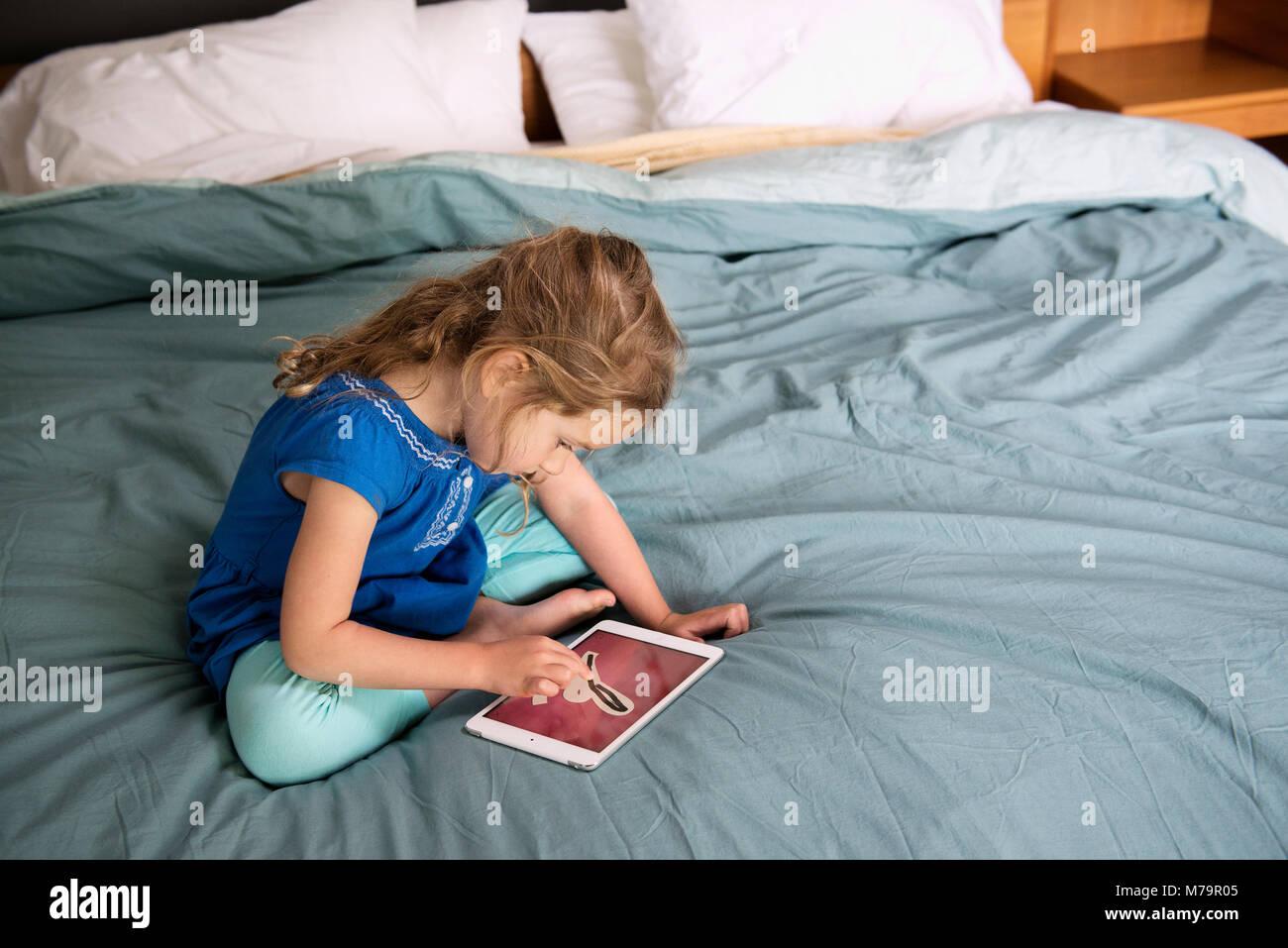 Una ragazza utilizzando un ipad mini per imparare a scrivere. Foto Stock