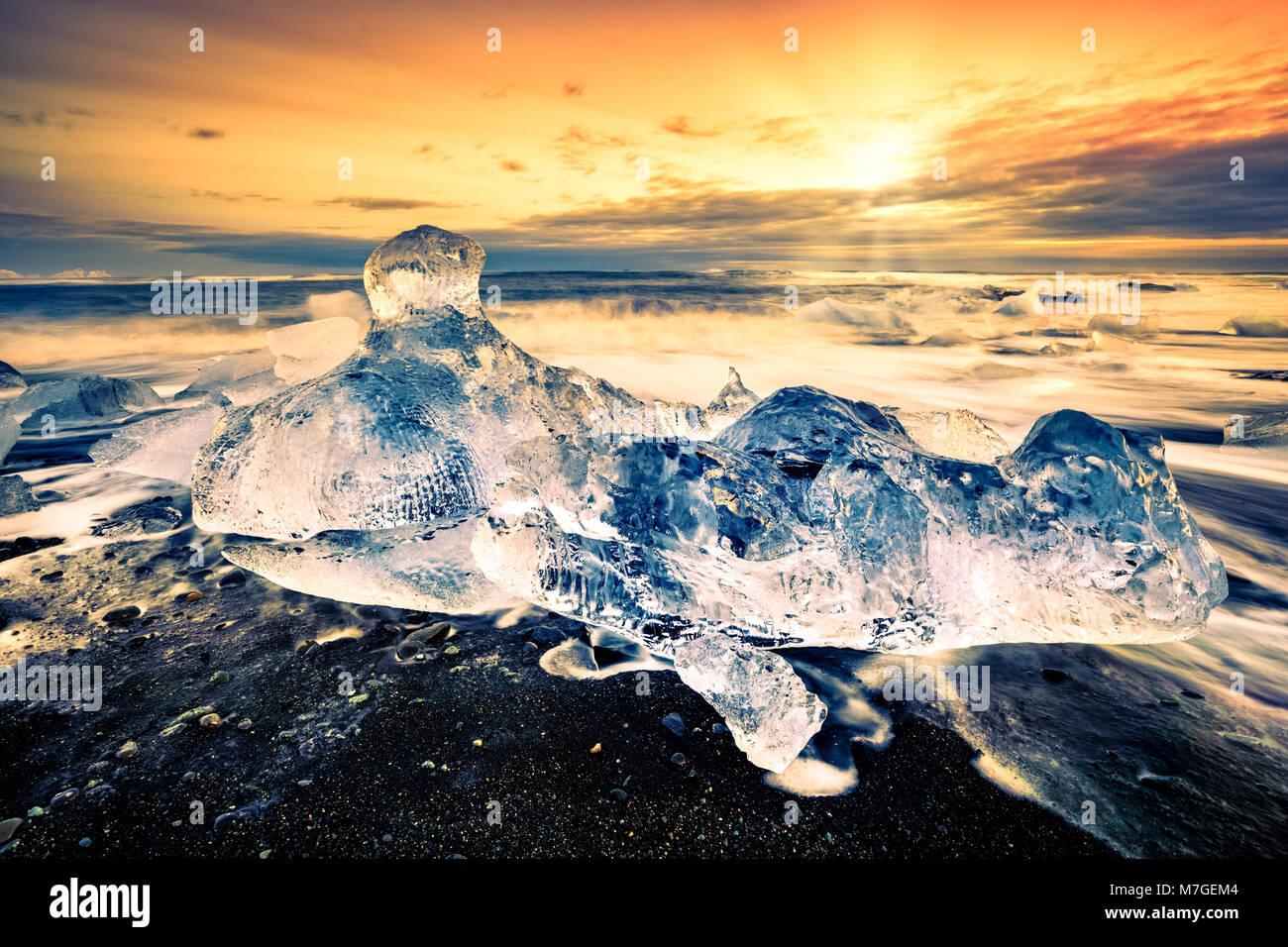 Vaganti iceberg sulla spiaggia di diamante, al tramonto, in Jokulsarlon, Islanda. Immagini Stock