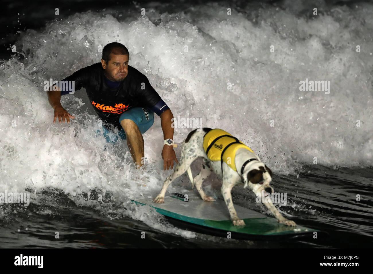 Un surfista con il suo animale domestico esegue una manovra durante la notte il surf mostra, nel quadro del maschio Foto Stock