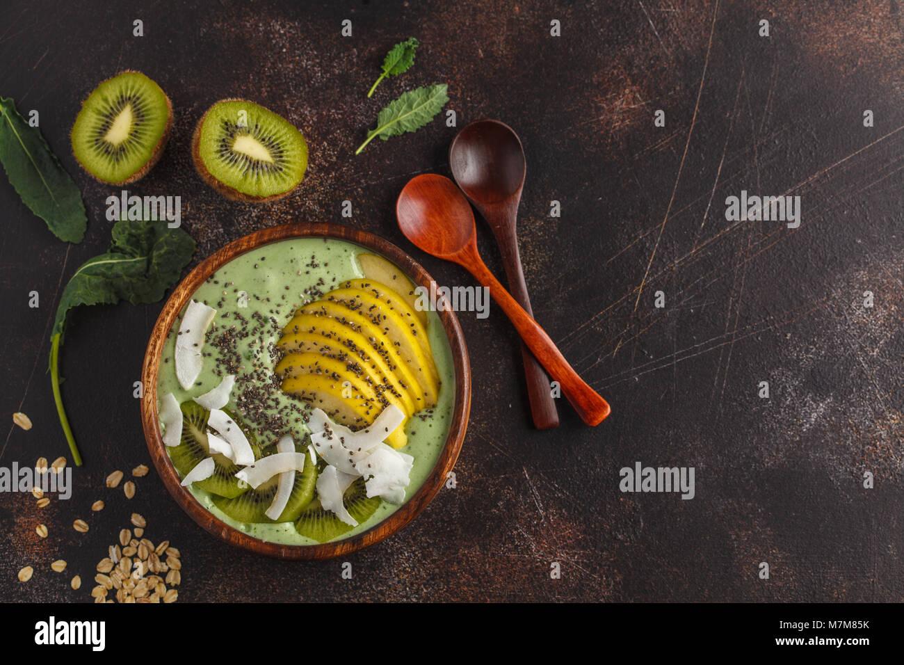 Cavolo verde frullato vegano ciotola con noce di cocco, chia, mela e kiwi. Sano cibo vegan concetto. Scuro dello Immagini Stock