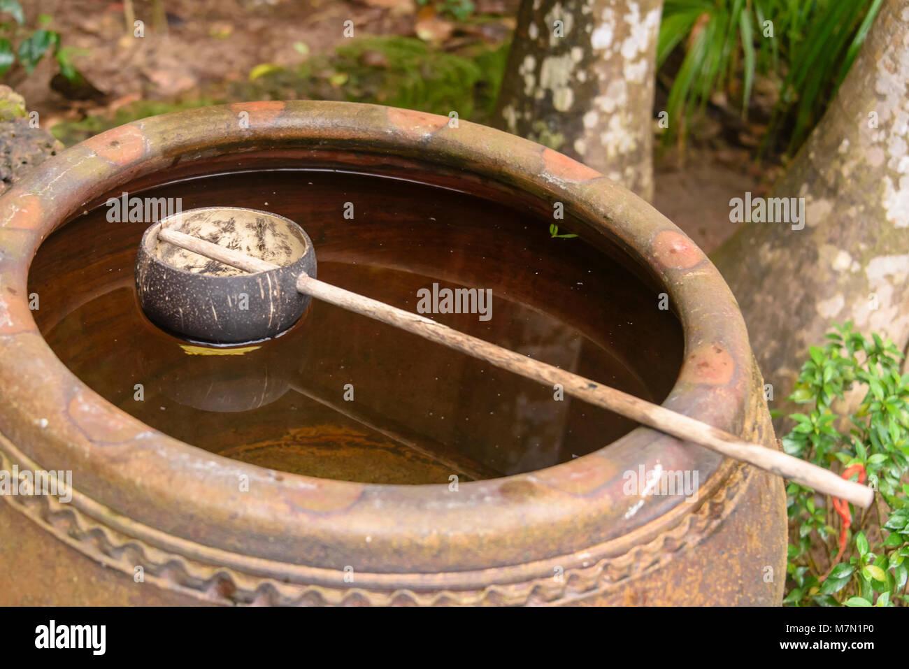 Una metà di guscio di noce di cocco con un bastone attaccato galleggiare su un urna di acqua piovana all'aperto, Immagini Stock