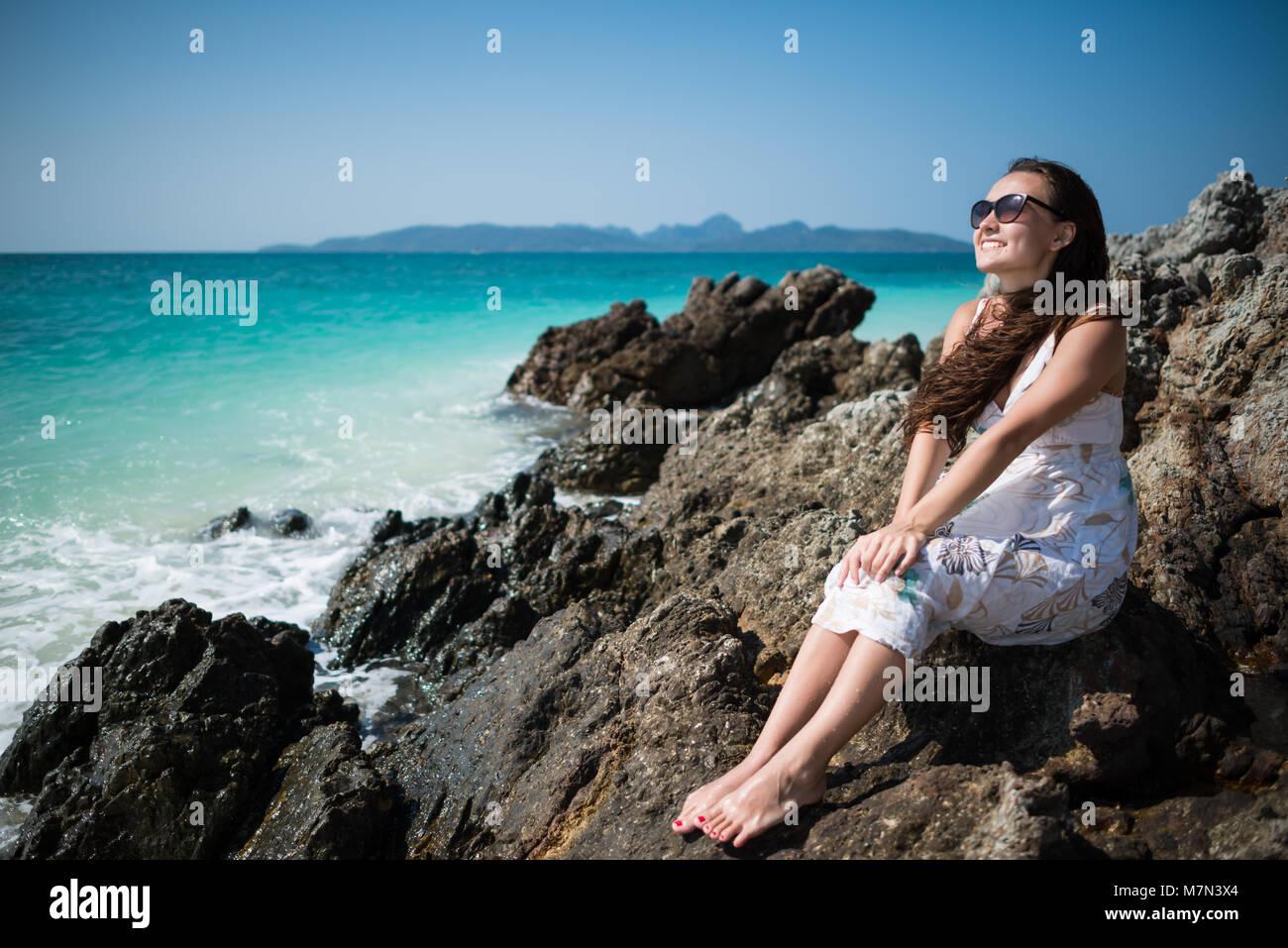 Giovane donna in abito siede sulla roccia sulla costa dell'oceano. Sorridente ragazza è godendo soleggiata Immagini Stock