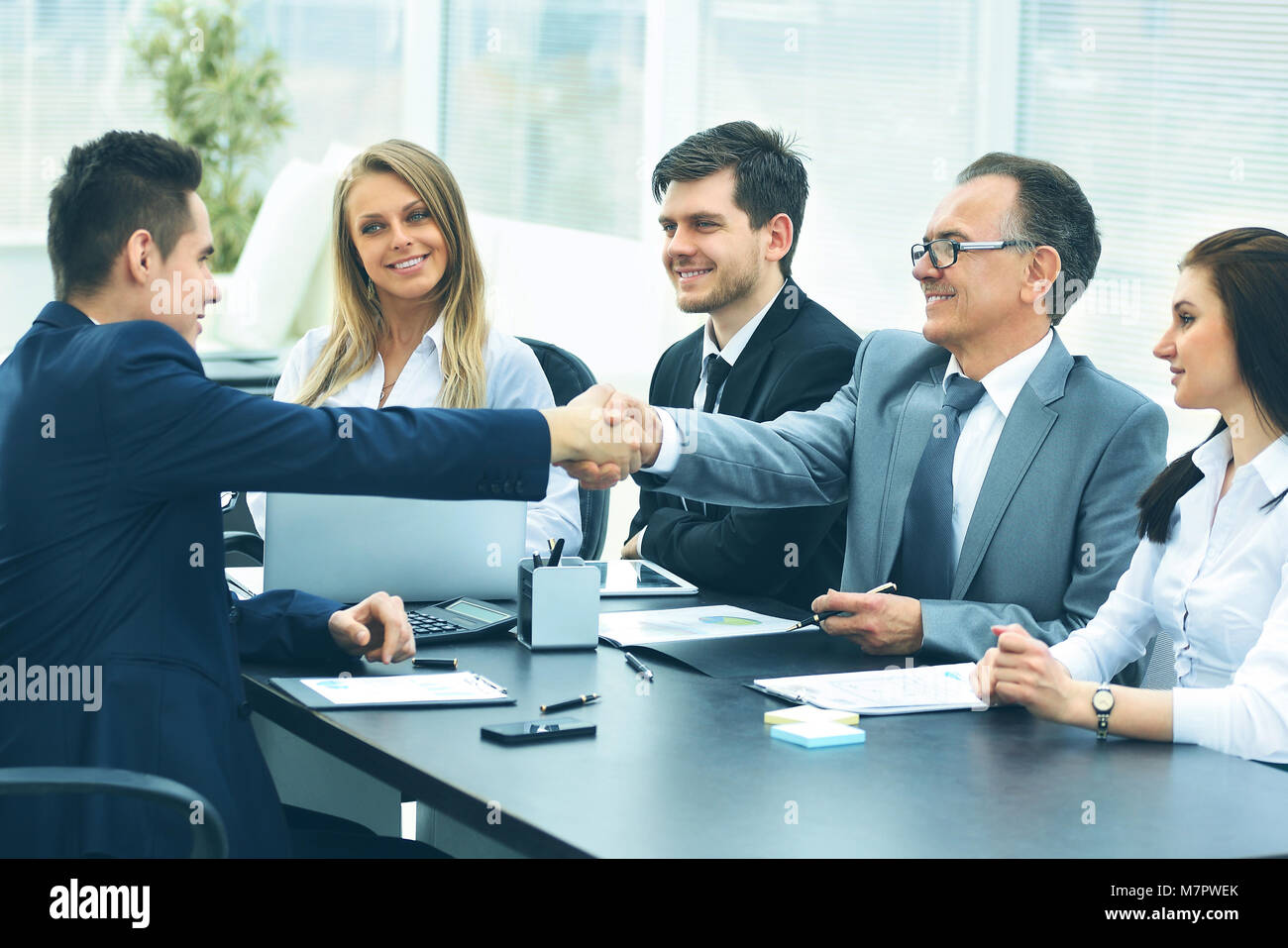 Business meeting al tavolo e la stretta di mano del partner aziendale Immagini Stock