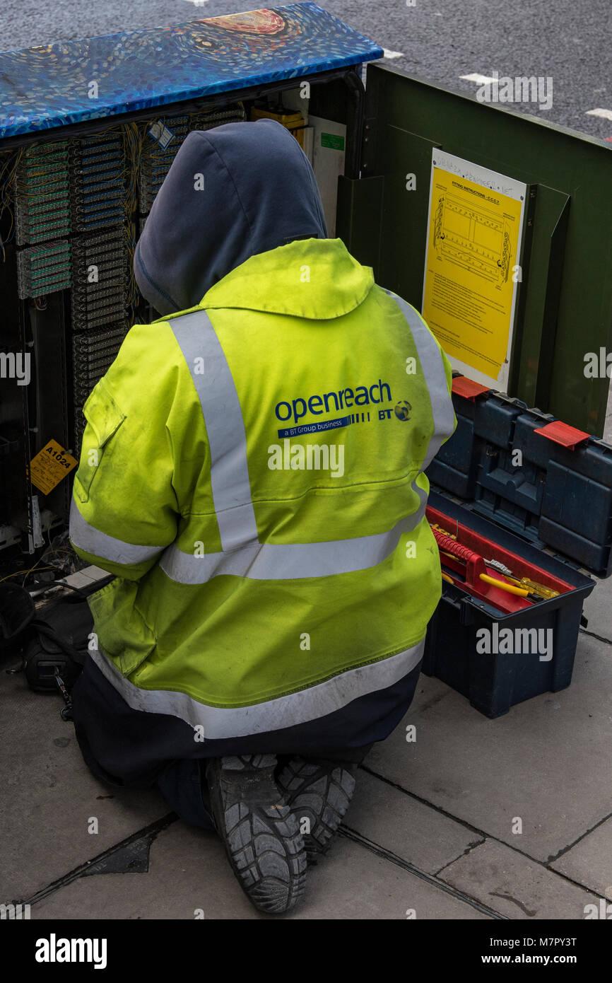 Un bt british telecom openreach telefono a banda larga ingegnere in un armadio di exchange che indossa un GIUBBETTO Immagini Stock