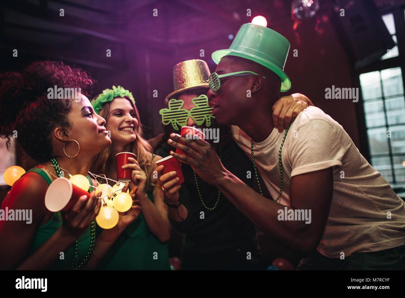 Multi-etnico gli uomini e le donne per divertirsi presso il bar. Gruppo di amici che celebra la festa di San Patrizio Immagini Stock