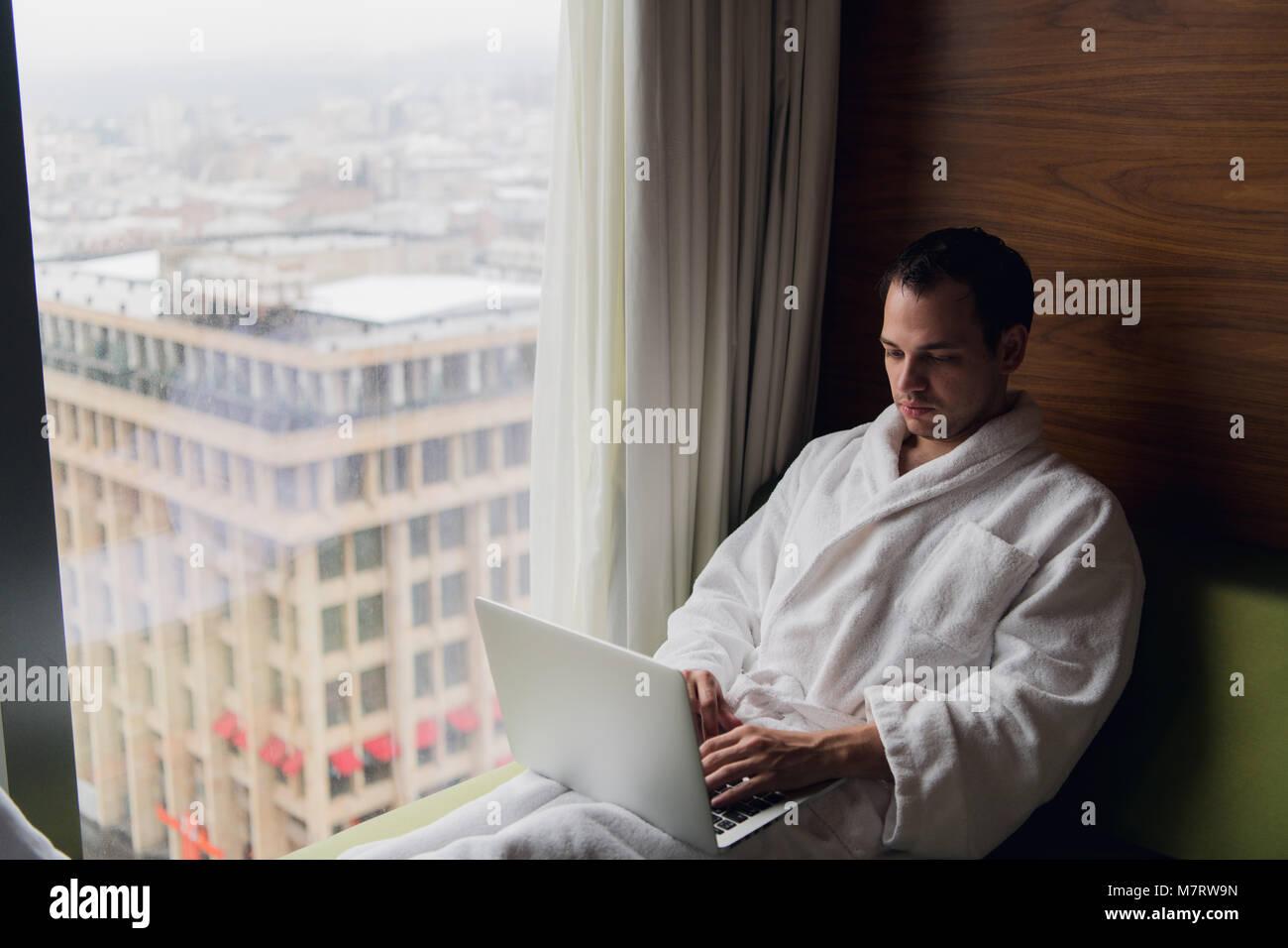 Giovane uomo libero professionista che lavora da casa su un computer portatile Immagini Stock