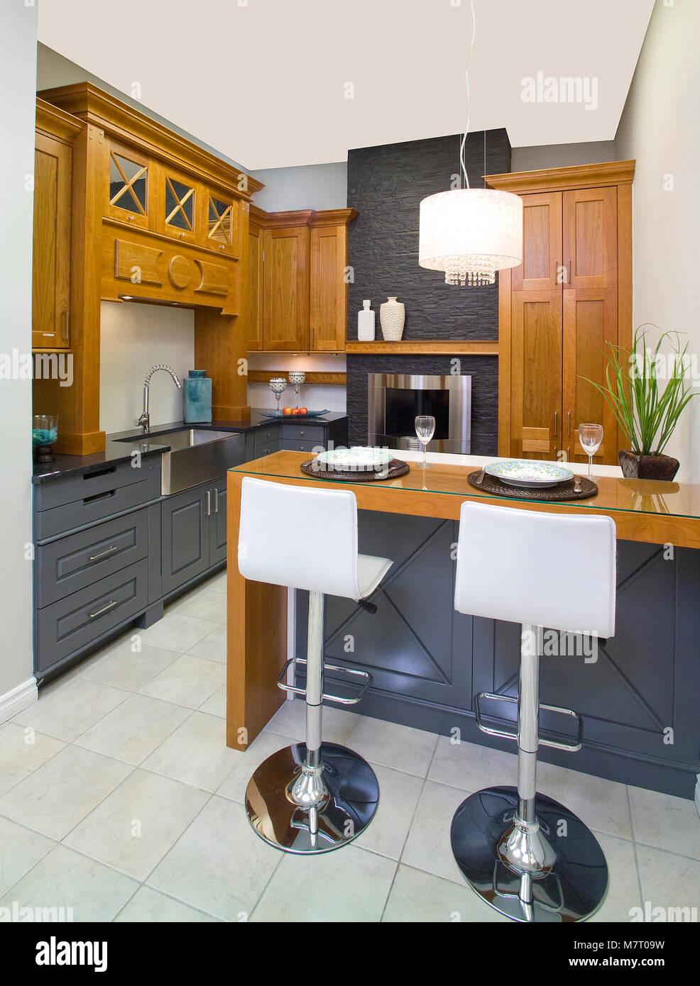 Grigio scuro e marrone cucina in legno con un isola e 2 sgabelli ...