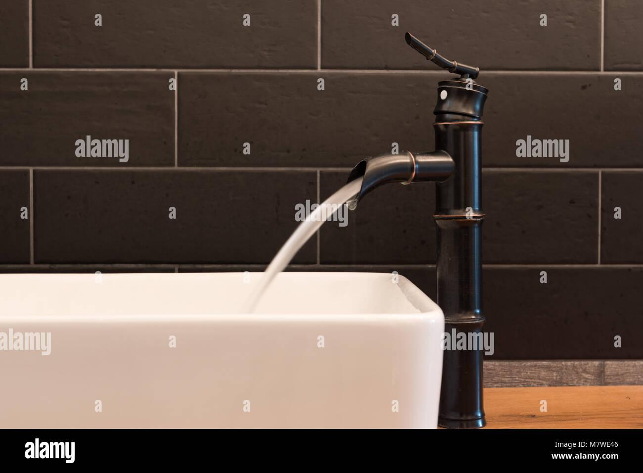 Moderno quadrato bianco il lavandino in bagno con piastrelle nere