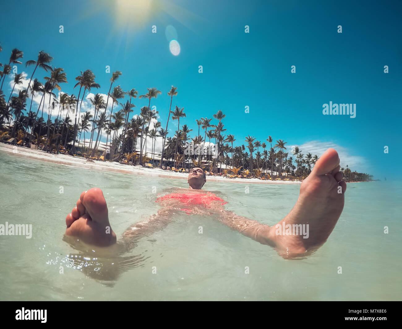 L'uomo godendo la sua vacanza estiva, acque turchesi del Mar dei Caraibi e la spiaggia di Punta Cana. Immagini Stock
