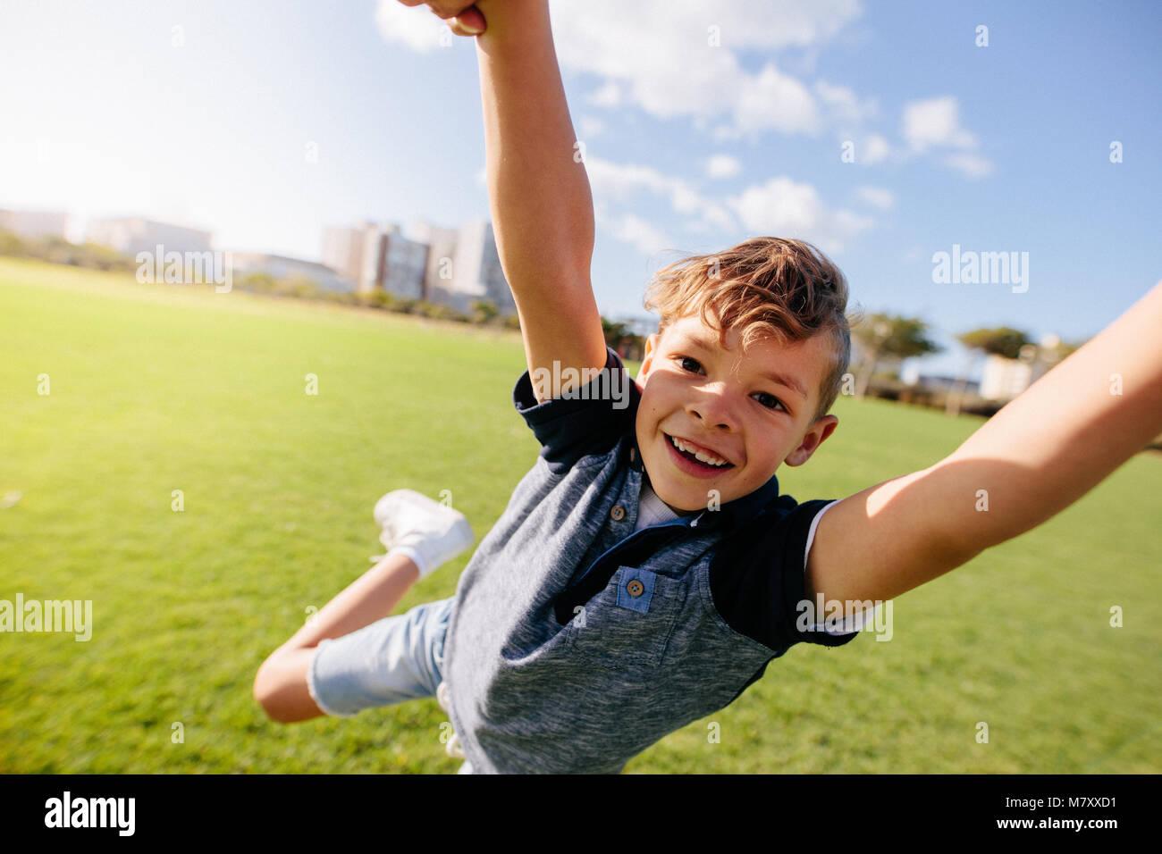 Close up di un ragazzo di saltare in aria a un parco. Allegro ragazzo gode di essere sollevata in aria durante il Immagini Stock