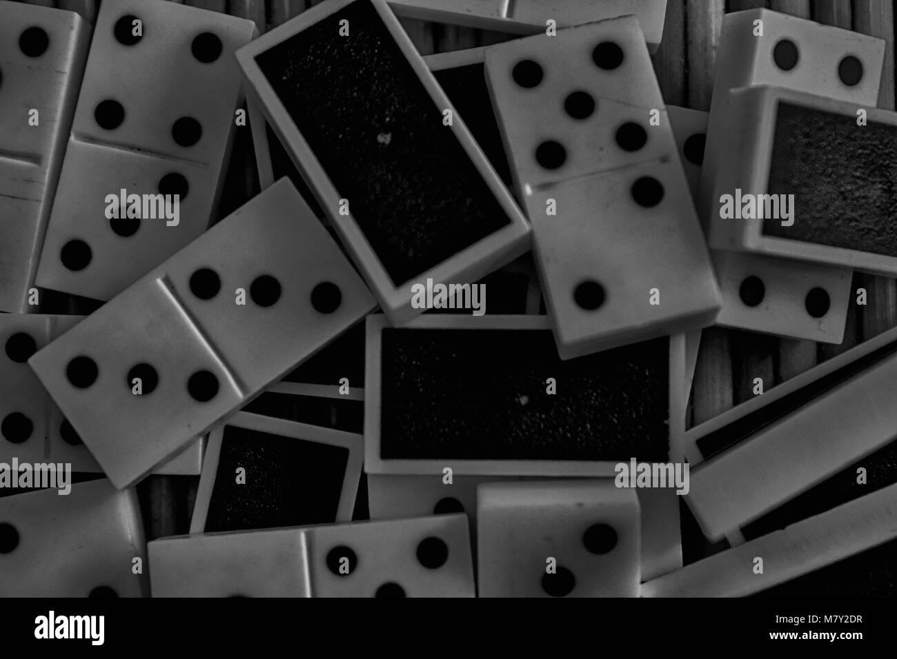 Monocromatico pila caotica di domino su pezzi di bambù in legno marrone sfondo tabella Immagini Stock