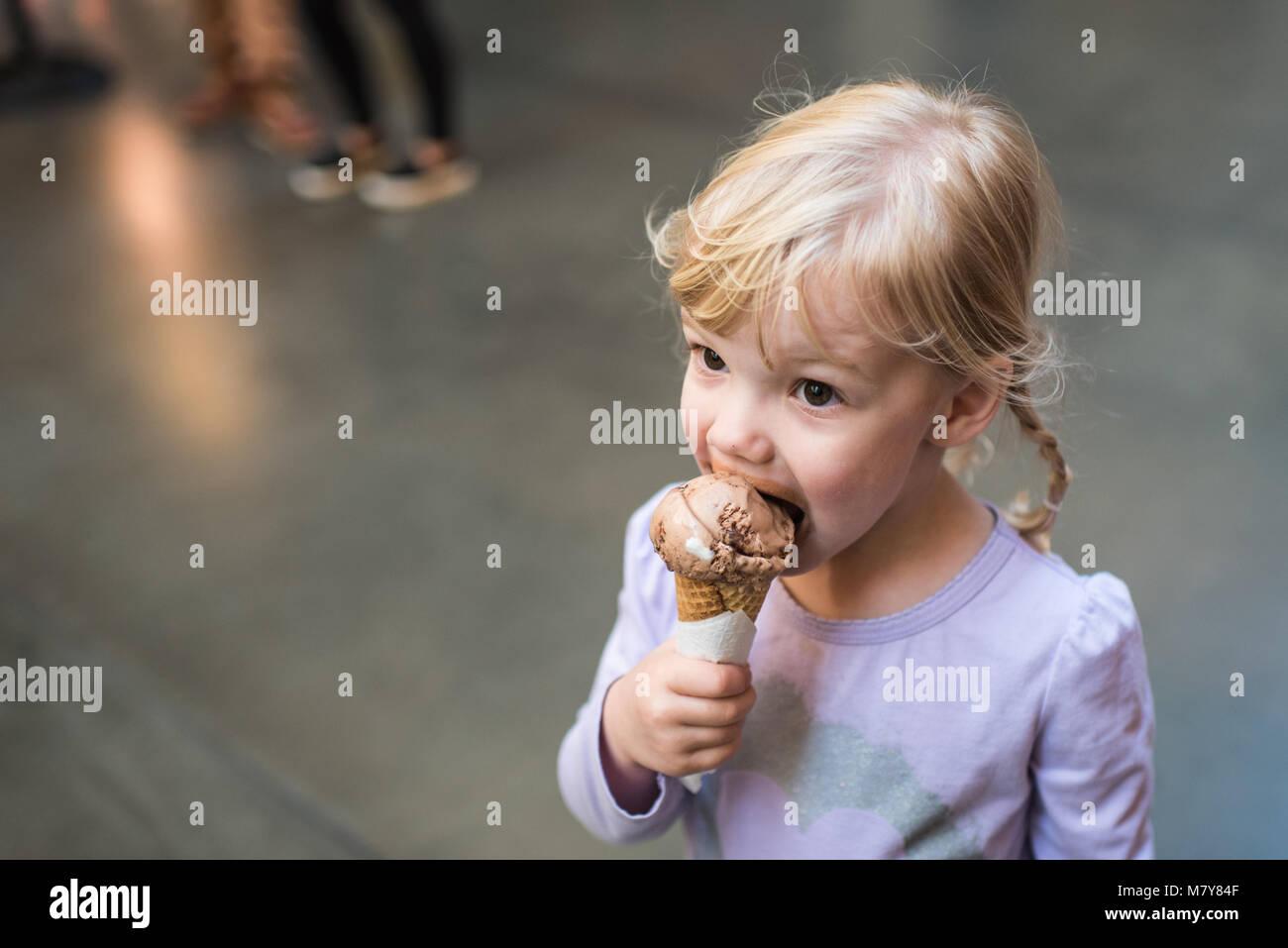 Bambino a mangiare il gelato in cono marketplace Immagini Stock