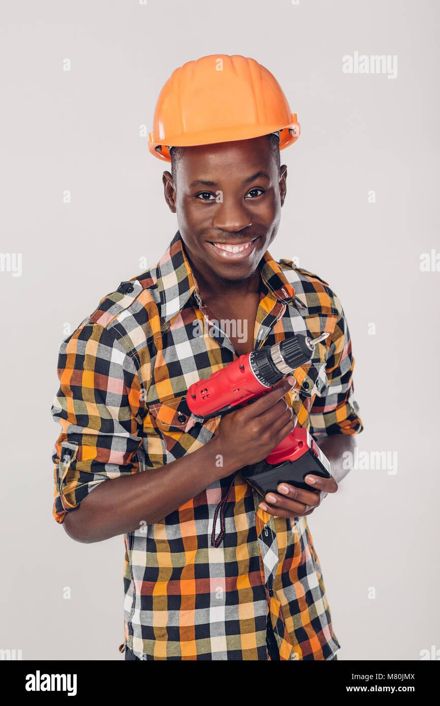 African American lavoratore utilizza cacciavite elettrico Immagini Stock