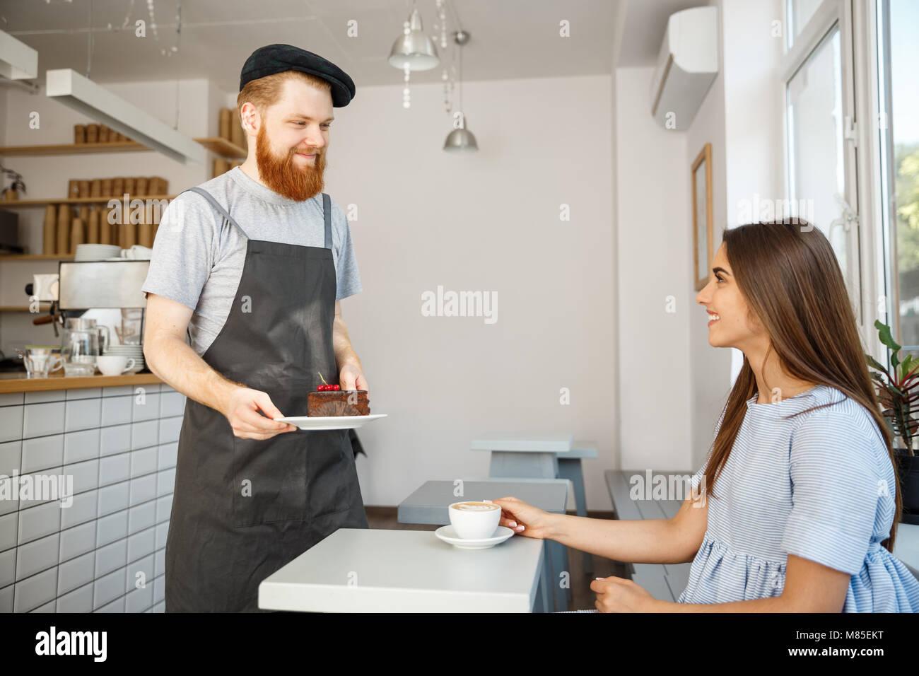 Caffè il concetto di Business - cameriere o barista dando una torta al cioccolato e parlare con caucasian bella Immagini Stock
