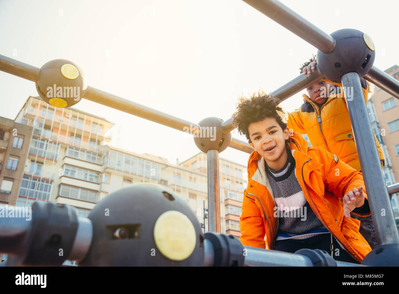 Dei bambini felici di arrampicata in un parco giochi urbano la costruzione in una giornata di sole Immagini Stock