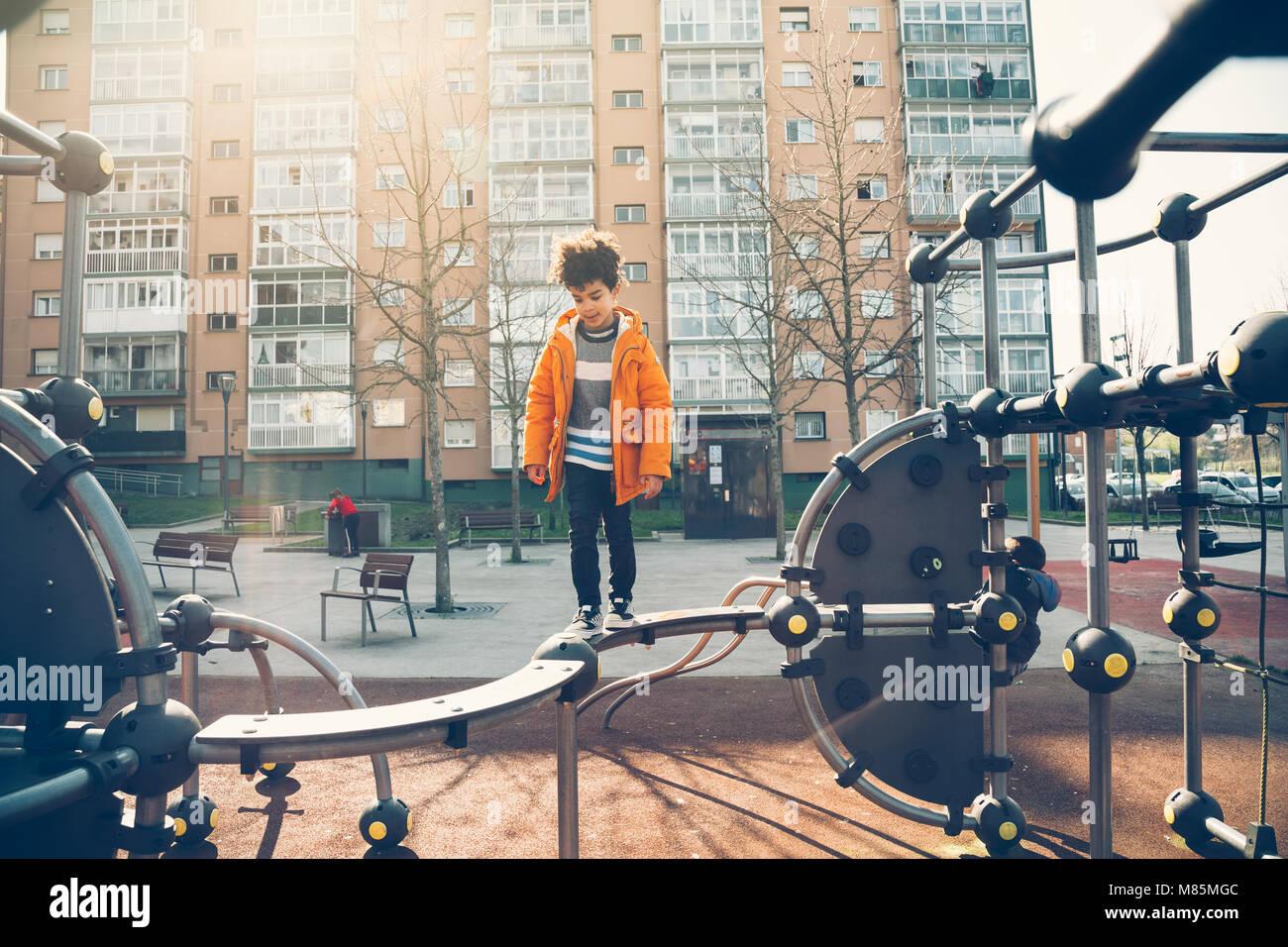 Carino piccolo ragazzo camminando la barra di bilanciamento in un parco giochi urbano in una giornata di sole Immagini Stock