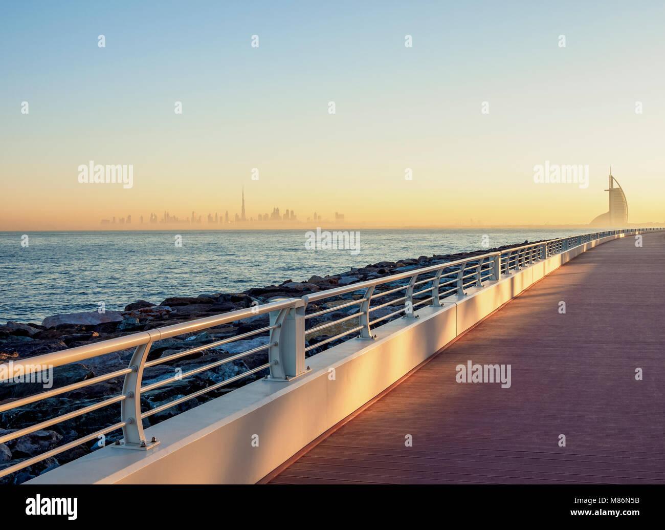 Palm Jumeirah Boardwalk e centro città Skyline di sunrise, Dubai, Emirati Arabi Uniti Immagini Stock
