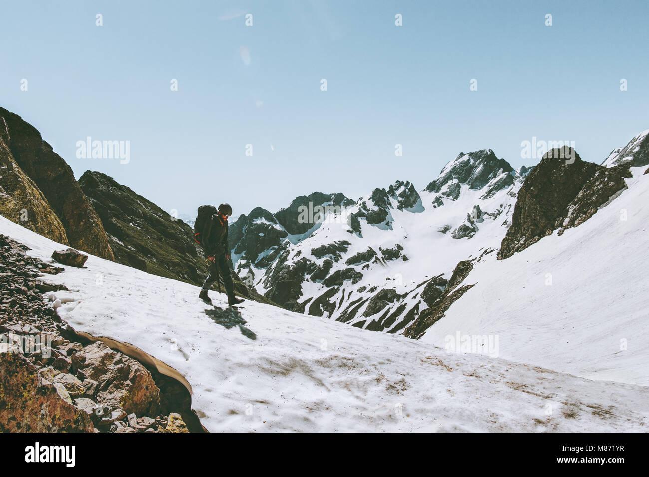 L'uomo viaggiatore con zaino trekking in montagna innevata di viaggio lo stile di vita di sopravvivenza concetto Immagini Stock