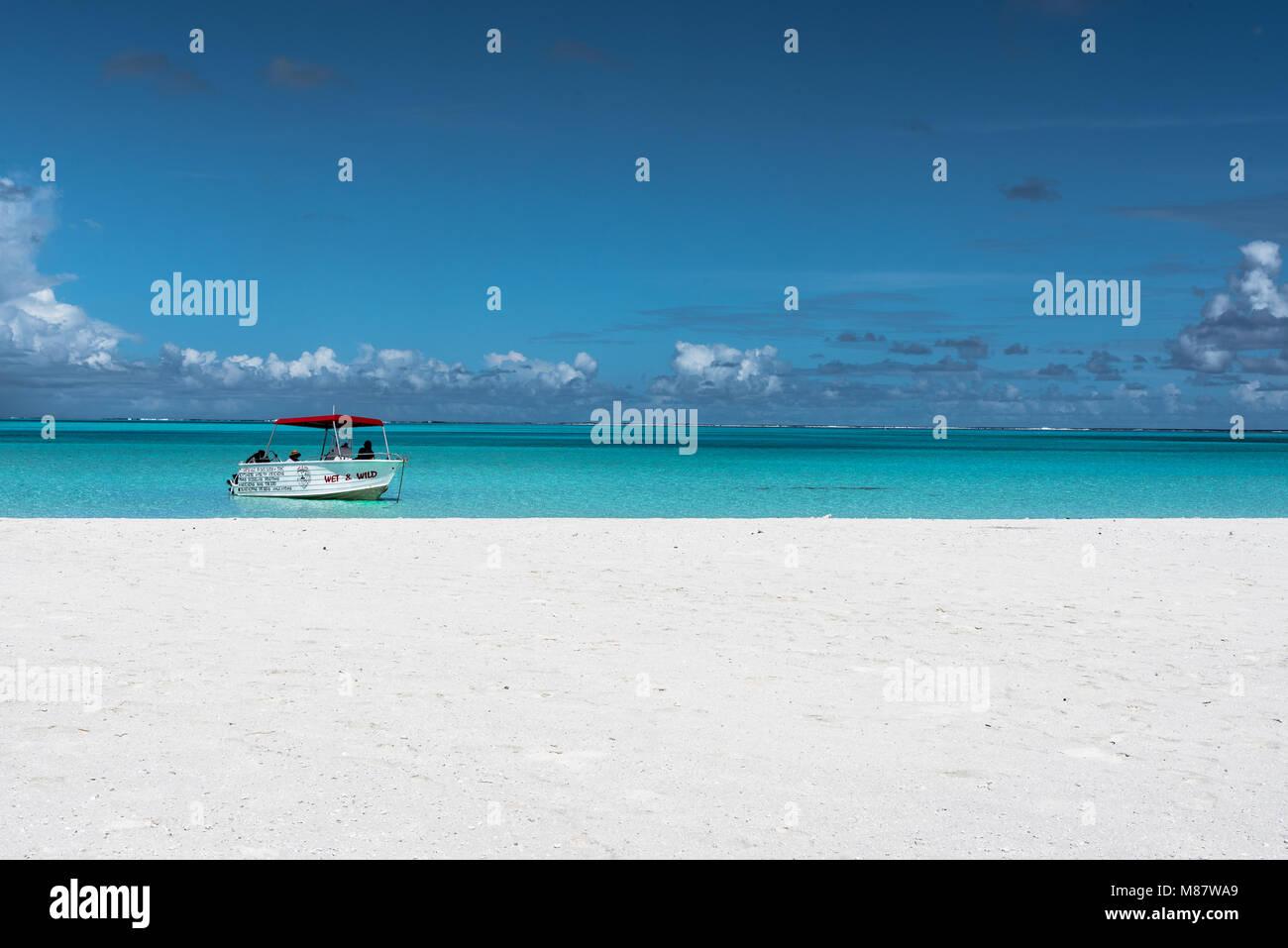 Maina Island, Isole Cook, Pacifico del Sud--marzo 14, 2018. Una barca di partito con i turisti è inserito appena Immagini Stock