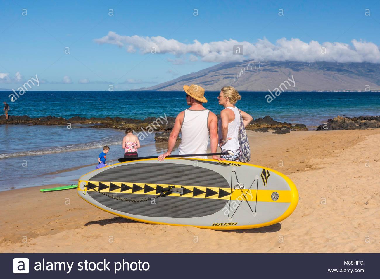 Coppia con paddleboard su Kamaole Beach Park 3 in Kihei sull'isola di Maui nello stato delle Hawaii USA Immagini Stock