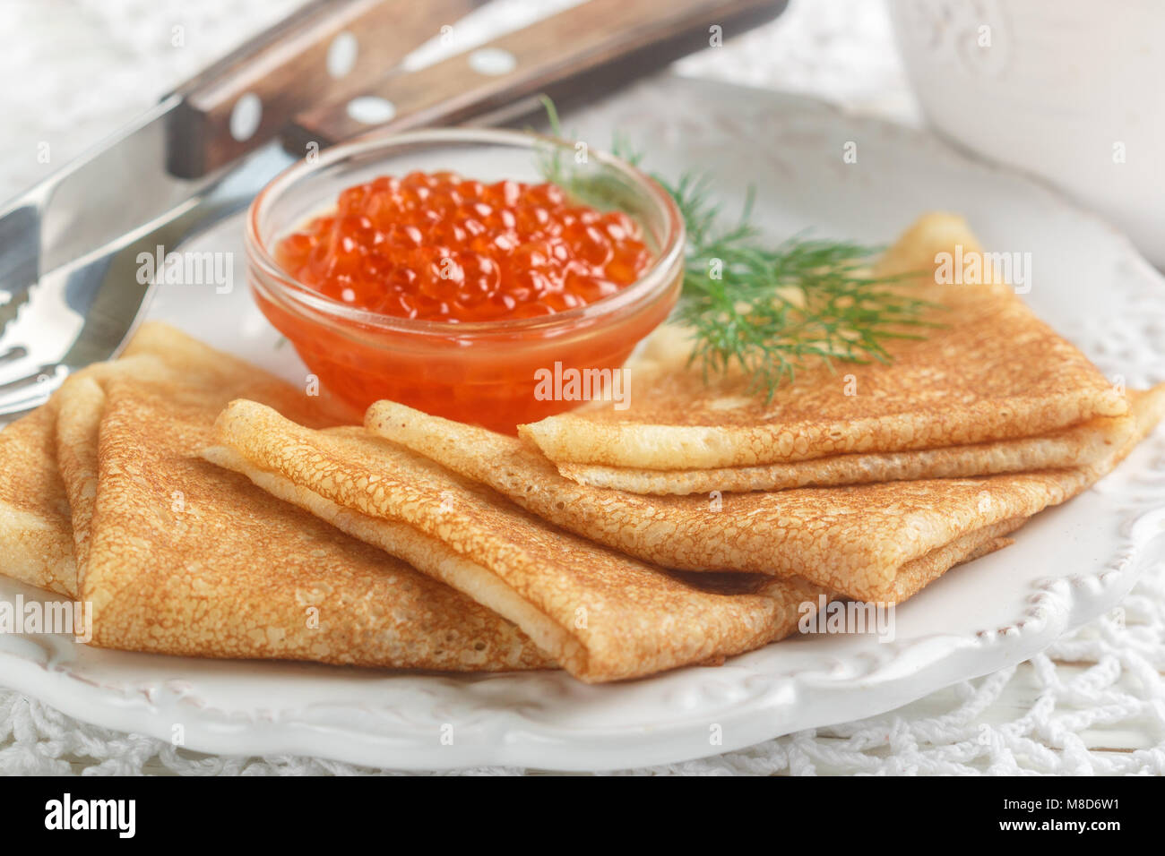 Tradizionale Frittelle Russe (blini ) con caviale di salmone su una piastra bianca. Messa a fuoco selettiva Foto Stock