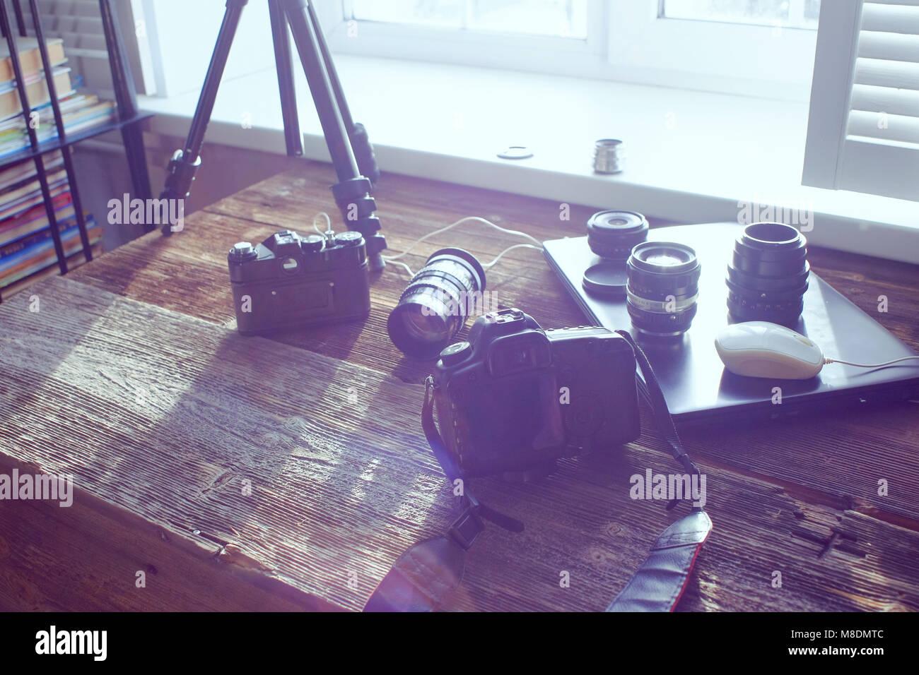 Ancora in vita di attrezzatura fotografica e portatile sul tavolo di fronte alla finestra Immagini Stock
