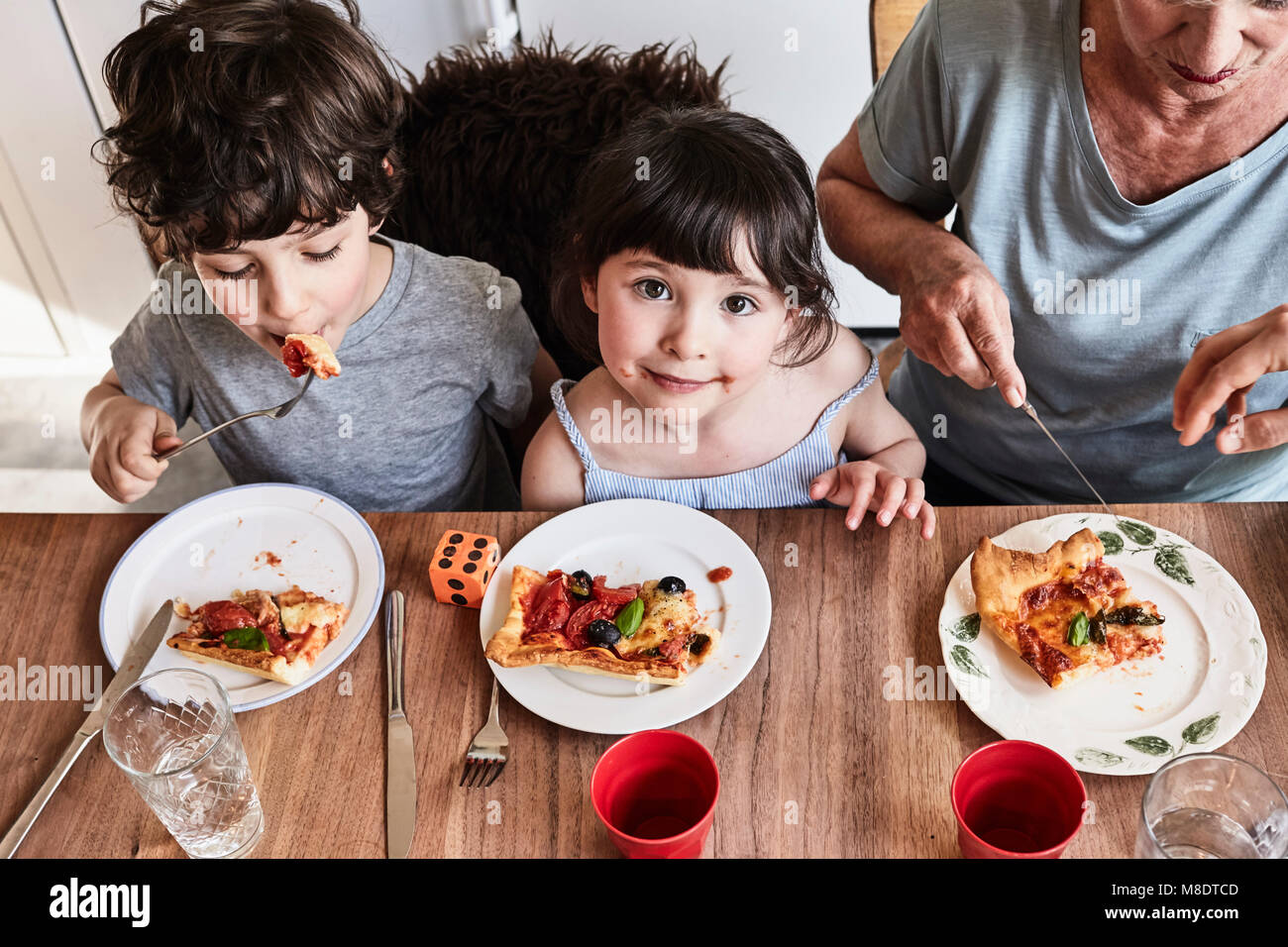 La nonna seduta al tavolo della cucina con i nipoti, mangiare la pizza, vista in elevazione Immagini Stock
