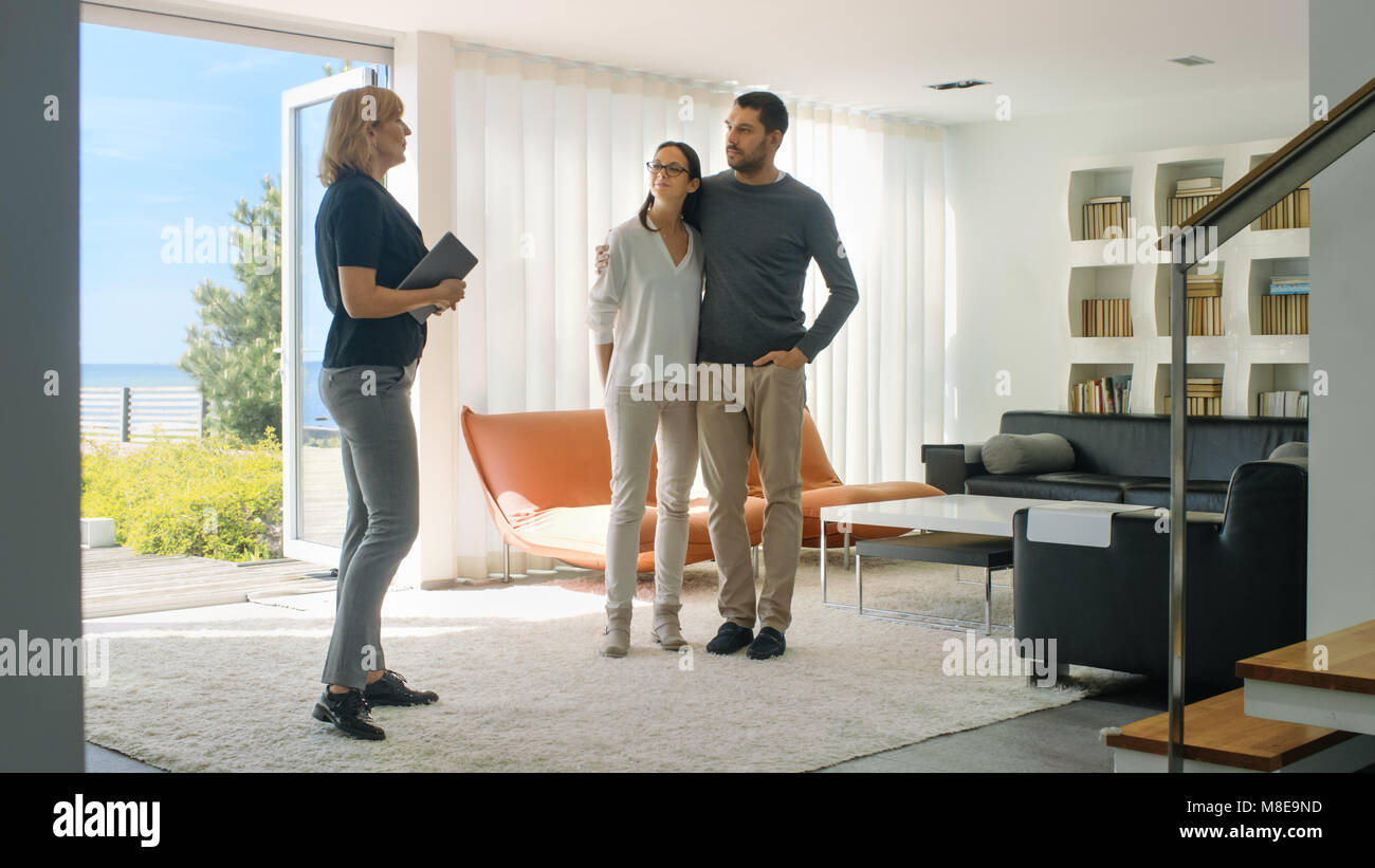 Agente immobiliare professionale mostra di stile moderno a casa per una bella giovane coppia che sono sul mercato Immagini Stock