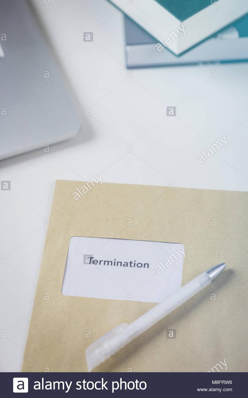La cessazione o la lettera di ridondanza in una busta marrone giacente su una scrivania bianca a fianco di una calcolatrice Immagini Stock